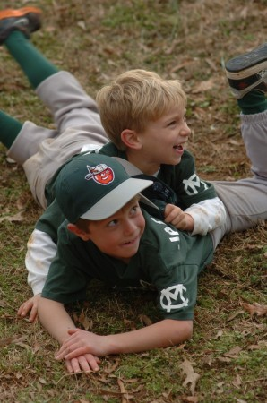 Bryce Matlock, top, and Oliver Jackoniski wrestle before the members of their baseball team, the Tin Caps, gathered for team introductions during Opening Day ceremonies at Murphey Candler Park on March 7.
