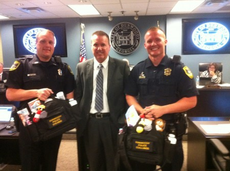 Dunwoody police officers Mark Stevens, left, and Anthony 'Kerry' Stallings, right, flank Police Chief Billy Grogan, who presented them with 'tactical diaper bags' to honor them for winning national attention for changing the diapers of two infants whose parents had been arrested for shoplifting.