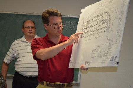 Lawyer Den Webb, foreground, and Dunwoody Chamber of Commerce board member Don Boyken, rear, point out elements of a proposed hotel development on property owned by the Spruill Arts Center. They presented the plans to the board of the Dunwoody Homeowners Association on April 13.