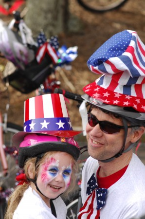 Audrey Dyche, 5, and her dad, Keith, road their bikes in the Dunwoody July 4 parade. Photo by Phil Mosier