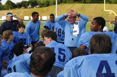 The Lovett School's head football coach Mike Muschamp, back right, discusses the game plan against  North Atlanta High School with his players on Aug. 15.