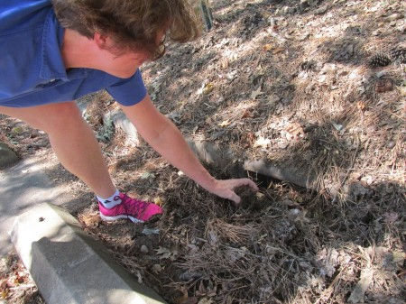 Sylvia McAdam points to debris clogging a storm drain outside the Sandy Springs Library.
