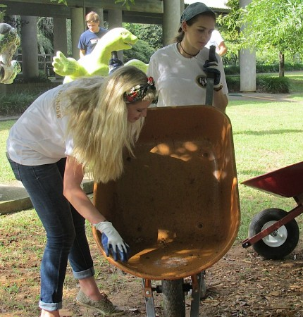 Mount Vernon 11th-grader Emily Hollis (left) and 12th-grader Arden Tahtinen empty mulch from a wheelbarrow.