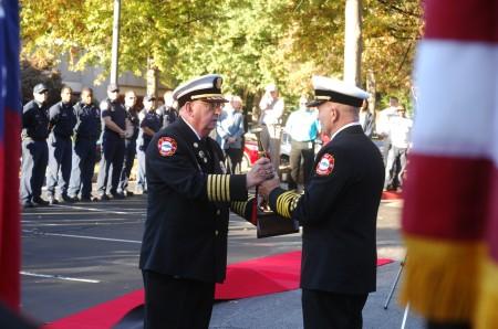 """Sandy Springs changing of command ceremony for its fire department Tuesday evening. Retiring Chief Jack McElfish passes the """"speaking trumpet"""" to incoming Chief Keith Sanders outside the Sandy Springs City Hall building."""