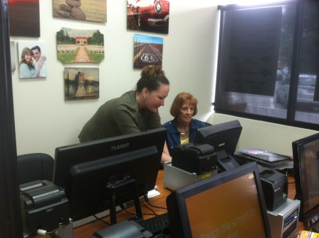 Dunwoody Photo lead instructor Indja Cornwell, left, assists customer Donna Hiller at the store's print lounge kiosk.