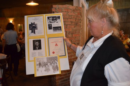 Sherry Wilhite holds up their yearbook, which opened with a photo of President John Kennedy, who was assassinated the fall of their senior year.