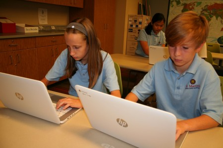 From left, 7th-graders Lily Steck, Kyra Graap (in back) and Jordan Wissman use their Chromebooks.