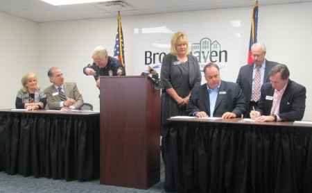 "City council members Rebecca Chase Williams and Joe Gebbia, Police Chief Gary Yandura, Mayor J. Max Davis and Councilman Bates Mattison sign the ""Not Buying It"" pledge while state Sen. Renee Unterman (fourth from right) and state Attorney General Sam Olens (second from right) look on."
