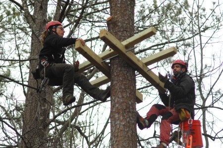 Maxime Risch, left, and Antoine Buliard, with Treetop Quest, create the tallest platform needed for the zip line portion of the obstacle course taking shape in Brook Run Park. The company has been asked to design, install and manage the adventure course for the park.