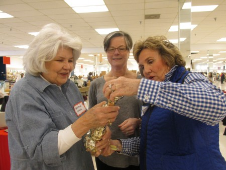 From left, Skipper Usher, Laura DeLong and Joan Plunkett take a close look at a goblet up for grabs at the Sandy Springs Society's annual Tossed Out Treaures sale, slated for March 27-28.