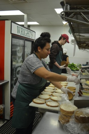 Diana Gomez, front, makes sandwiches. The shop turns out 300 to 400 sandwiches a day, and also sells lasagna and other take-out foods.