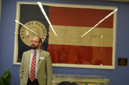 """E. Rivers Principal Matthew Rogers stands in front of a Georgia state flag that was """"rescued"""" by 11-year-old John Maltby when the school burned to the ground in 1948."""