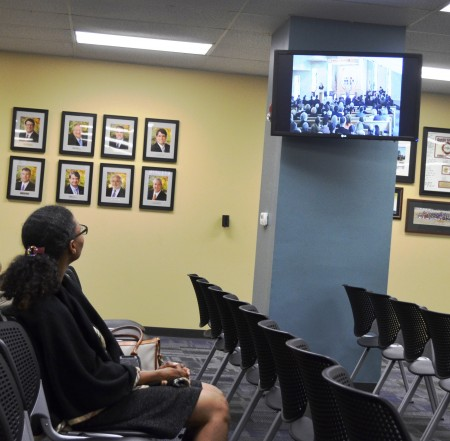 Michele McIntosh-Ross watches Galambos' funeral from Sandy Springs City Hall.