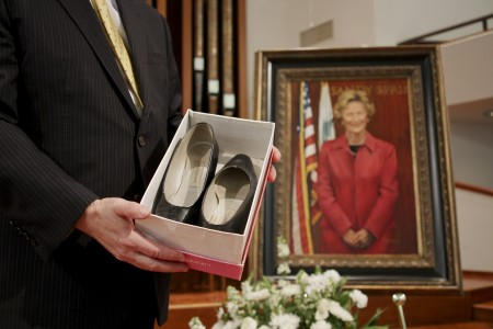 Mayor Rusty Paul is presented with a pair of Eva Galambos' shoes during a memorial hosted by city officials April 24. Photo by Isadora Pennington.
