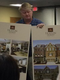 Clif Poston of Traton Homes shows proposed townhome designs to community members during a zoning meeting April 28.