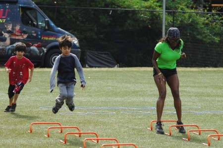 Marguerite Rippy, right, fitness director for Sandy Springs Parks and Recreation, and twins Daniel and Benjamin Straley, 8, check out an obstacle course at Hammond Prk May 16 during National Kids to Parks Day.