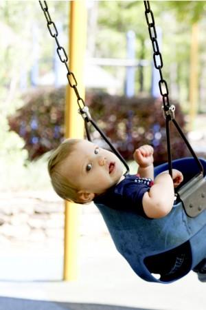 Brooks Rosencrans, 1, enjoys being pushed in a swing at Brook Run Park's playground. Photo by Ellen Eldridge