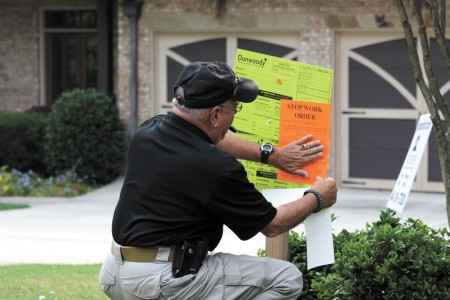 Dunwoody Code Compliance Officer Tom LaPenna places a stop work order at a residence. Photo by Ellen Eldridge.