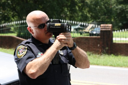 Dunwoody Officer Chris Irwin checks speeds with a radar detector July 16 along Tilly Mill Road. A total of 12 citations and three warnings were issued to drivers during a pedestrian safety detail. Photo by Ellen Eldridge