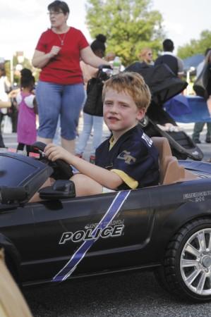 "Joe Gewertz, 6, in the ""police"" car he and his father David Gewertz built."
