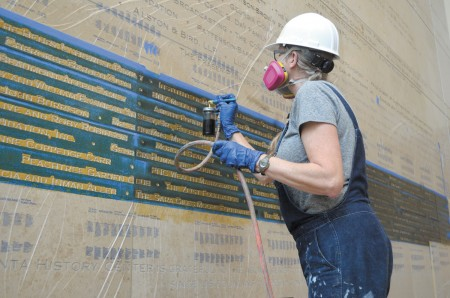 Nancy Ballew highlights names of major donors carved into limestone walls in the Atlanta History Center's new 5,300-square-foot atrium.