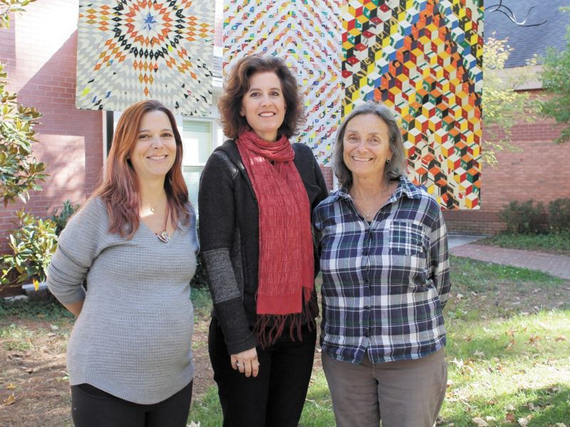 """Robin Critz, Evelyn Edmeades, and Judy Schwarz pose in front of """"Ask the Wind,"""" a permanent art piece by Greely Myatt of Memphis, TN. The work was purchased with funds raised from Art Visions. Photo by Isadora Pennington."""