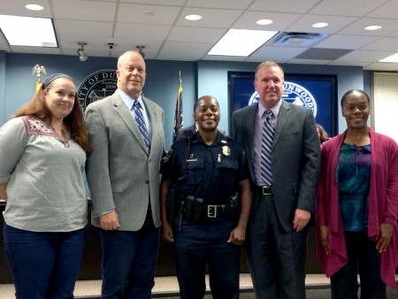 Officer Rashida Moore (center) stands with Mayor Mike Davis (to her right) and Chief Billy Grogan (to her left) after having been sworn in as a member of the Dunwoody Police Department Oct. 26.