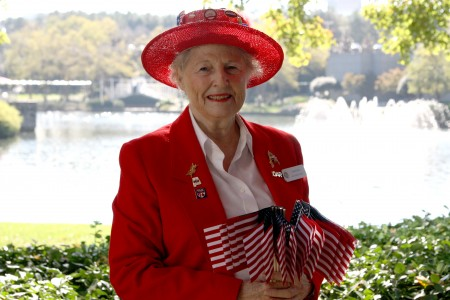 Nancy Huey, a member of the Sandy Springs chapter of Daughters of the American Revolution, hands out flags during the Sixth Annual Veterans Day Tribute Nov. 11 at Concourse. Photo by Ellen Eldridge.