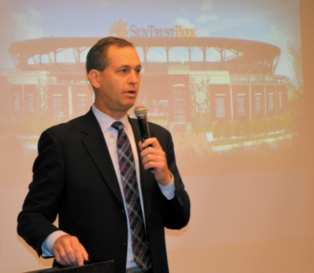 Braves executive vice president Derek Schiller talks to the BBA backed by an image of new SunTrust Park.