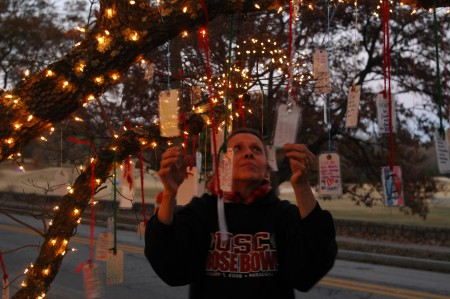 4000 block of Powers Ferry Road; Saturday December 5, 2015 12:00pm - 6:00pm. The Wishing Tree. Made by Debra and John Minkley. Debra hanging, and untangling wishes, as John holds the ladder.