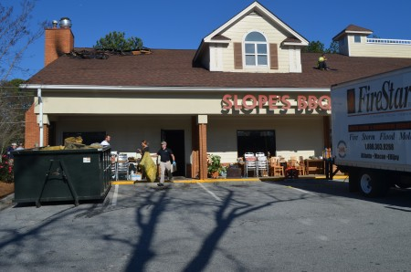 Workers clean Slopes BBQ after a fire damaged the restaurant on Dec. 16.