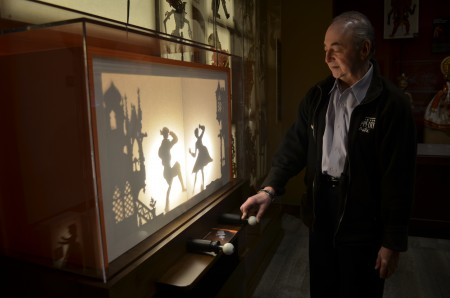 "Puppeteer Vince Anthony, executive director of the Center for Puppetry Arts in Atlanta, works a shadow puppet display in the center's museum. ""Puppetry can be a touchstone to so many kinds of things,"" he said. (Photo Joe Earle)"
