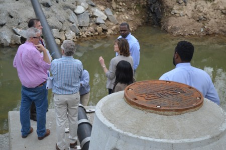 Residents and city officials examine a recently replaced sewer line during a tour of Atlanta Memorial Park.