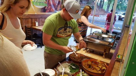 """""""Bus crawl"""" attendees dig in at Plaza Fiesta on April 27. (Photo John Ruch)"""