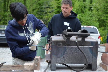 Adem Wijewickrema twists a metal bar as blacksmith Andrew Crawford instructs students at Springmont School in Sandy Springs.
