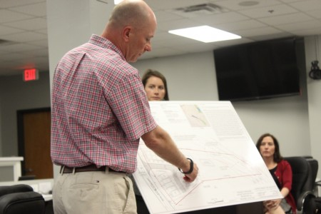 Mike Embry explains proposed plans to construct 17 townhomes along Ashford-Dunwoody Road. Looking on are zoning attorney Jill and Brookhaven City Councilmember Linley Jones. (Photo Dyana Bagby)