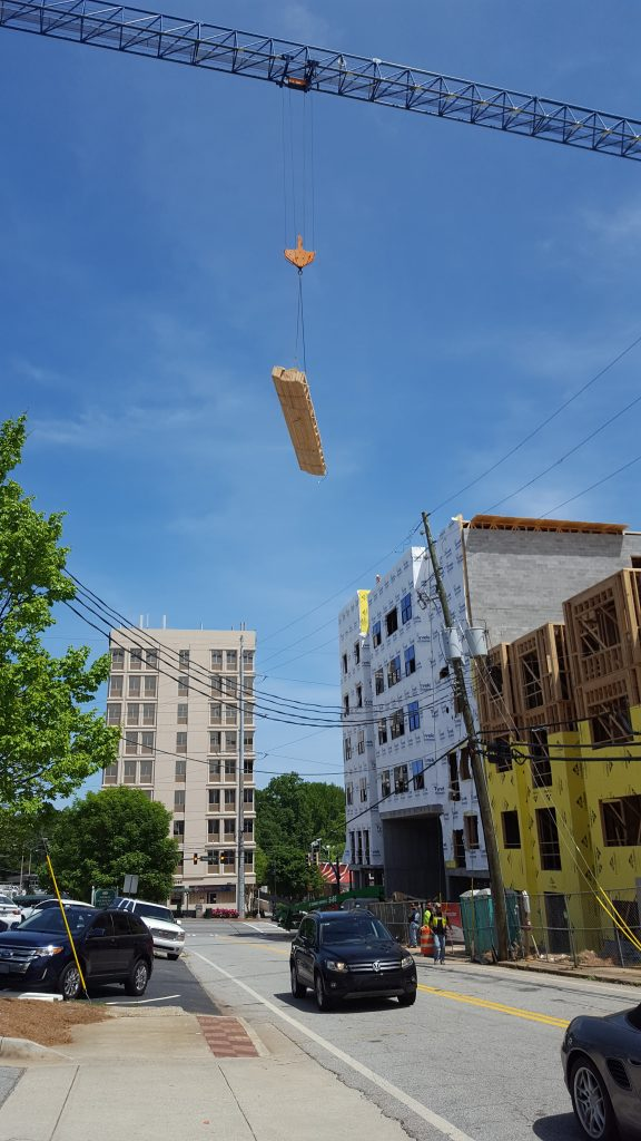 A load of wooden building frames dangles over a street in Sandy Springs on April 29.