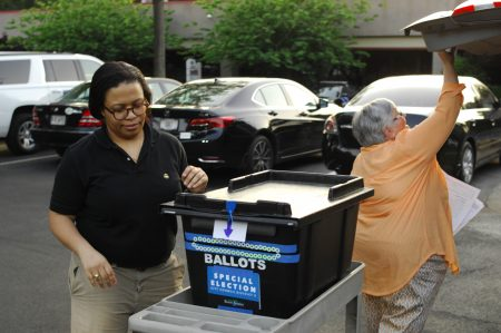 Poll volunteer April Persons, left, and poll manager Alicia Volk deliver ballots to City Hall on May 24 after the City Council District 3 special election. (Photo Phil Mosier)