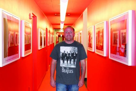"""Radio 105.7 DJ and promotions manager Knox, pictured in a station hallway lined with concert photos, says radio now works on the """"paper plate theory"""" - people consume content really fast and throw it away. (Photo John Ruch)"""