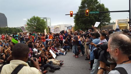 Protesters sit in Peachtree Road to block the entrance to the Lenox Square Mall. (Photo John Ruch)