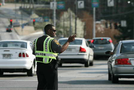 An off-duty DeKalb County Police officer hired for traffic control by the Perimeter Community Improvement Districts in a photo featured on the PCIDs website.