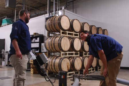 Distillery co-owner Jim Chasteen, left, and distiller Justin Manglitz pump the mash from the fermenter to the wash still.  Bourbon aging in barrels are stacked behind them. (Photo Phil Mosier)