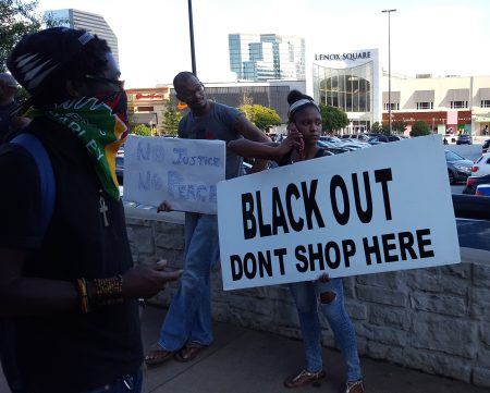A protester carries a sign calling for a boycott of Lenox Square Mall. (Photo John Ruch)