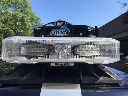 A model Sandy Springs Police car atop its real-life counterpart. (Photo Sgt. Forrest Bohannon/SSPD)