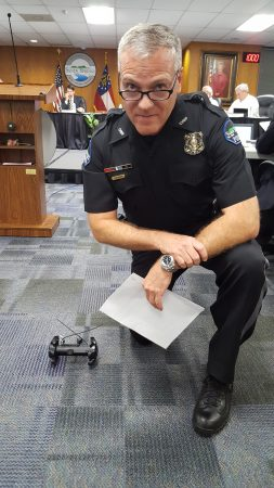 Sandy Springs Police Chief Ken DeSimone poses with a Throwbot XT robot shortly after the City Council approved accepting grant funding to purchase a second one Sept. 20. (Photo John Ruch)