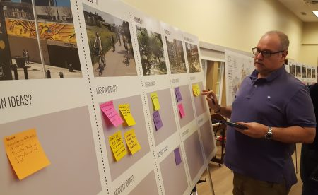 """A resident adds a note to the """"connectivity"""" display at the """"BUCKHEAD REdeFINED"""" master plan meeting Oct. 17 at Atlanta International School. (Photo John Ruch)"""