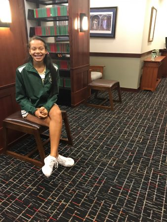 Andi Rozelle sits atop her winning carpet design at Holy Spirit Preparatory School. (Special)