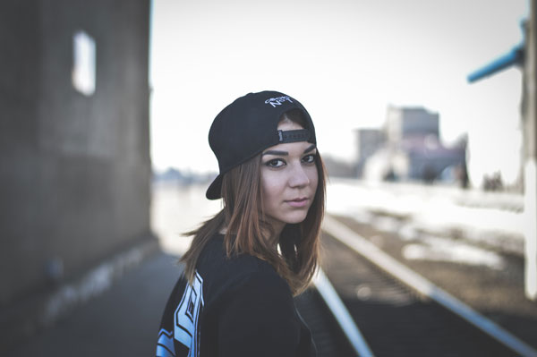 Young woman with a baseball cap on near railway tracks