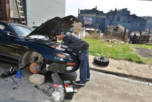 A man works on his car across the way from the former steel mill