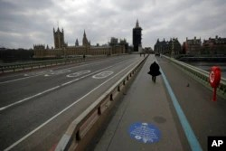 FILE - People pass over a quiet Westminster Bridge, backdropped by the scaffolded Houses of Parliament and the Elizabeth Tower, known as Big Ben, in London, during England's third coronavirus lockdown, March 23, 2021.
